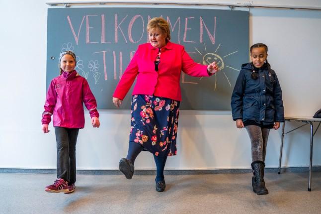 Nórska premiérka Erna Solberg ukazuje, ako možno niekoho pozdraviť s dodržaním odstupu. / Foto: Håkon Mosvold Larsen / NTB