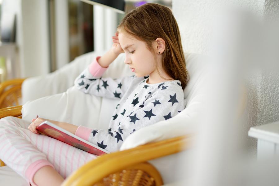 Čítanie kníh je výbornou príležitosťou na stíšenie aj pri starších deťoch. / Foto: Bigstock