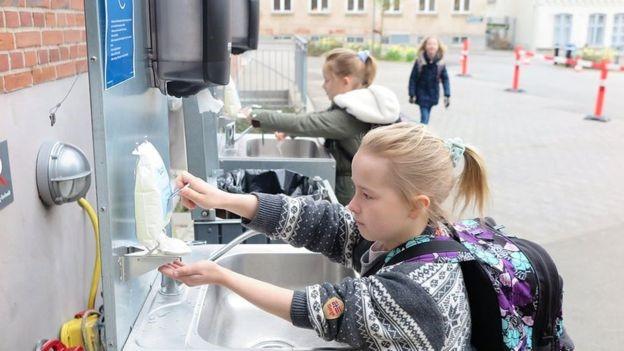 Dánske deti si počas prestávky vonku v areáli školy umývajú ruky. / Zdroj: BBC